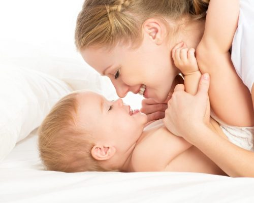 happy family mother and baby having fun playing, kissing laughing on the bed