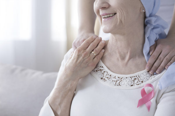 Breast cancer awareness concept - pink ribbon on a sick, older woman and supportive hands on her shoulder